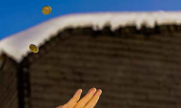 shallow focus photography of person catching two gold colored coins